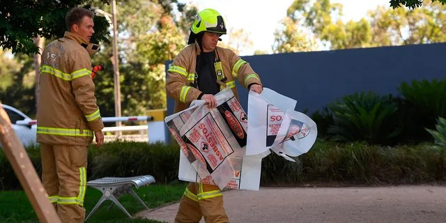 A firefighter is seen carrying a hazardous material bag into the South Korean consulate in Melbourne. (Associated Press)