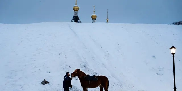 A man prepares a horse to ride tourists during a cold winter day at a hill, near the Assumption Cathedral in the small Russian town of Dmitrov.