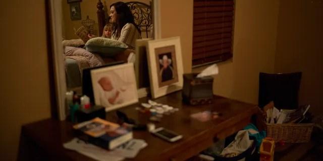 Landon Biggers' longtime girlfriend, Megan Dealbert, reads a bedtime story to their daughter, Aubrey, in La Quinta, Calif.