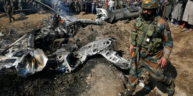 An Indian army soldier walks past the wreckage of an Indian aircraft after it crashed in Budgam area, outskirts of Srinagar, Indian controlled Kashmir, Wednesday, Feb.27, 2019. (AP Photo/Mukhtar Khan)