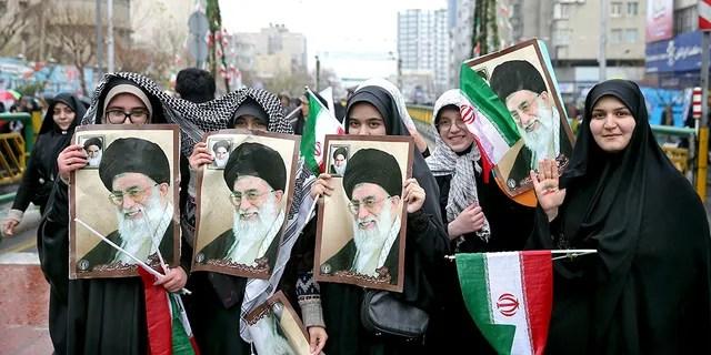 Iranian women hold up portraits of Iranian Supreme Leader Ayatollah Ali Khamenei, during a rally marking the 40th anniversary of the 1979 Islamic Revolution, in Tehran, Iran, Monday, Feb. 11, 2019.