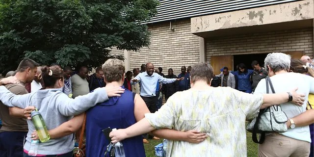 A pastor leads people in prayer at the site of a walkway collapse at the Driehoek High School in Vanderbijlpark, South Africa, Friday, Feb. 1, 2019. At least 3 students were killed and scores injured at the school near Johannesburg, a South African official said.