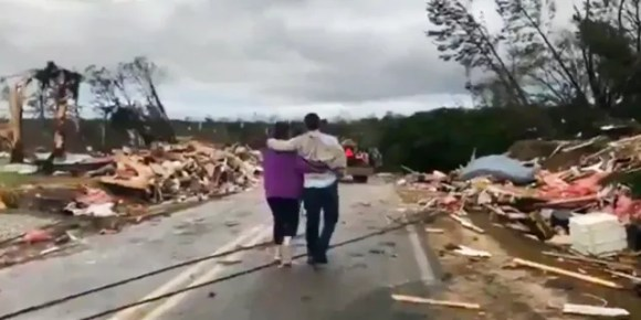 People walk amid debris in Lee County, Ala., after a tornado struck in the area Sunday, March 3, 2019.