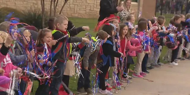 The kids of Frazier Elementary School cheered on police and fire escorts. (Fox 4)