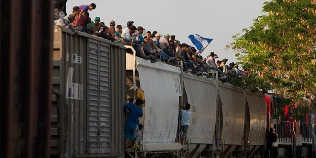 Central American migrants ride atop a freight train during their journey toward the U.S.-Mexico border, in Ixtepec, Oaxaca State, Mexico