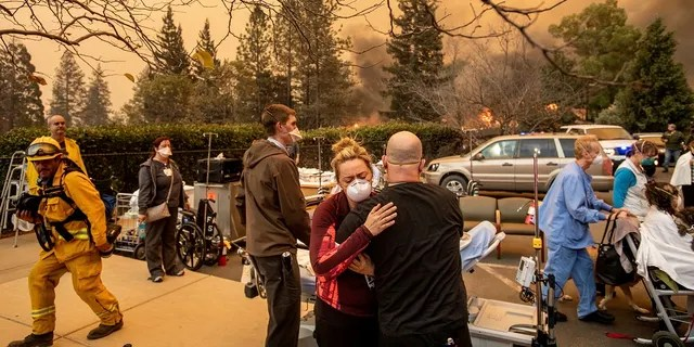 This Nov. 8 photo shows Nurse Cassie Lerossignol hugging a co-worker as the Feather River Hospital burns, victim of the Camp Fire raging in Paradise, Calif. (AP Photo/Noah Berger, File)
