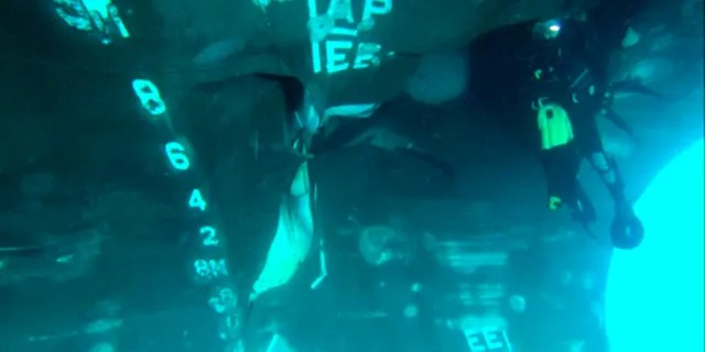 This undated photograph from the United Arab Emirates' Mission to the United Nations released Thursday, June 6, 2019, shows a diver investigating the damage done to the Saudi-owned oil tanker Al Marzoqah off the coast of Fujairah, United Arab Emirates.