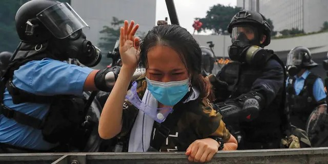 A protester reacts as she tackled by riot police during a massive demonstration outside the Legislative Council in Hong Kong, Wednesday, June 12, 2019. Hong Kong police have used tear gas and high-pressure hoses against thousands of protesters opposing a highly controversial extradition bill outside government headquarters.