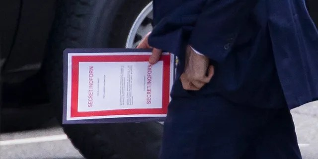 Outgoing Acting Defense Secretary Patrick Shanahan carries a document labeled secret as he arrives for a meeting with President Donald Trump about Iran at the White House Thursday. (AP Photo/Alex Brandon)