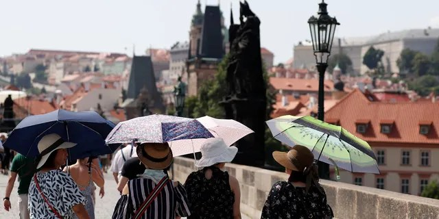 Tourists use umbrellas to shield themselves from the sun as they cross the medieval Charles Bridge on a hot day in Prague, Czech Republic, Wednesday, June 26, 2019.