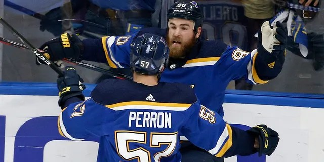 St. Louis Blues center Ryan O'Reilly (90) celebrates with David Perron (57) after O'Reilly scored his second goal of the game during the third period of Game 4 of the NHL hockey Stanley Cup Final against the Boston Bruins Monday, June 3, 2019, in St. Louis. (AP Photo/Scott Kane)