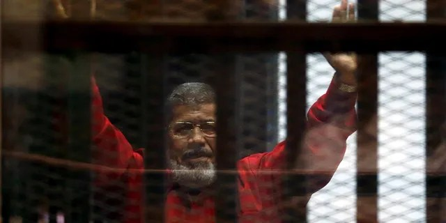 In this 2015 photo, Egypt's deposed president Mohamed Mursi greets his lawyers and people from behind bars at a court hearing.