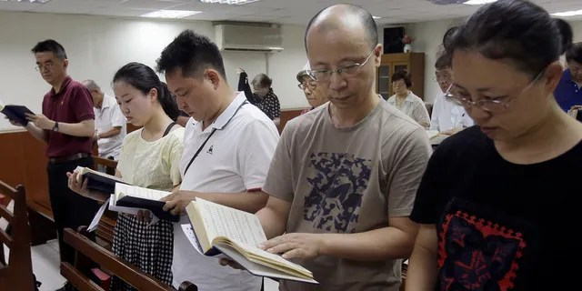 In this Sunday, July 7, 2019, photo, from right; Ren Dejun, Liao Qiang, Peng Ran and Ren Ruiting follow a hymn book during service at a church in Taipei, Taiwan. The Sunday service this week at an unassuming church in Taiwan was especially moving for one man, Liao Qiang. It was the first time he had worshipped publicly since authorities shut down his church in China seven months ago. (AP Photo/Chiang Ying-ying)