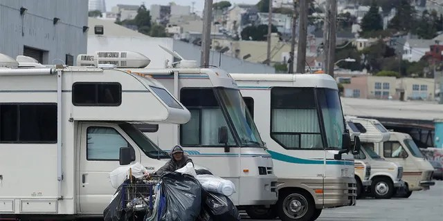 A person pushes a cart past parked RVs along a street in San Francisco on June 27, 2019. A federally mandated count of homeless in San Francisco increased 17 percent in two years, driven in part by a surge of people living in RVs and other vehicles.
