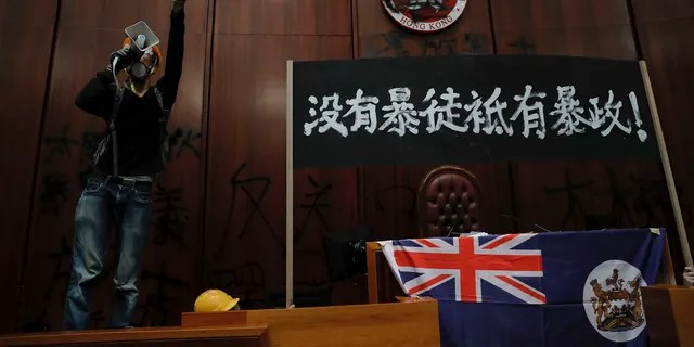 A protester shouts next to a defaced Hong Kong emblem and a banner reads