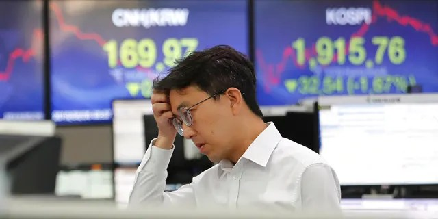 A currency trader watches monitors at the foreign exchange dealing room of the KEB Hana Bank headquarters in Seoul, South Korea, Monday, Aug. 26, 2019. (AP Photo/Ahn Young-joon)