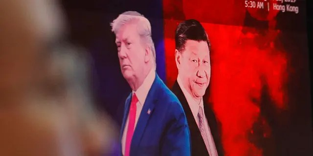 A computer screen shows images of Chinese President Xi Jinping, right, and U.S. President Donald Trump as a currency trader works at the foreign exchange dealing room of the KEB Hana Bank headquarters in Seoul. (AP Photo/Ahn Young-joon)