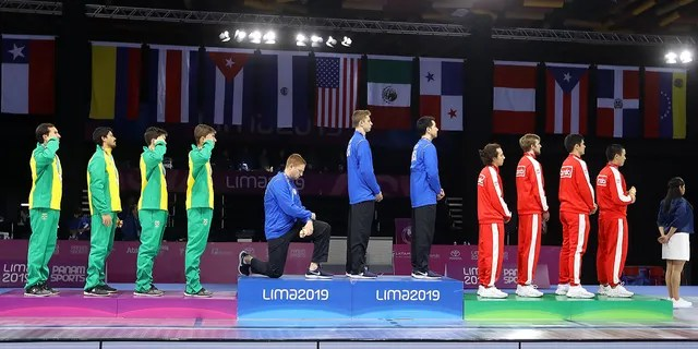 Gold medalist Race Imboden of United States takes a knee during the National Anthem Ceremony in the podium of Fencing Men's Foil Team Gold Medal Match Match on Day 14 of Lima 2019 Pan American Games at Fencing Pavilion of Lima Convention Center on August 09, 2019 in Lima, Peru. (Photo by Leonardo Fernandez/Getty Images)
