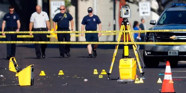 Evidence markers rest on the street at the scene of a mass shooting Sunday, Aug. 4, 2019, in Dayton, Ohio.