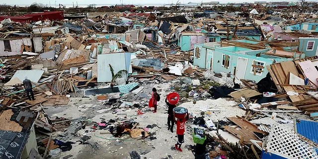 People search for salvageable items as they make their way through an area destroyed by Hurricane Dorian at Marsh Harbour in Great Abaco Island, Bahamas on Thursday.