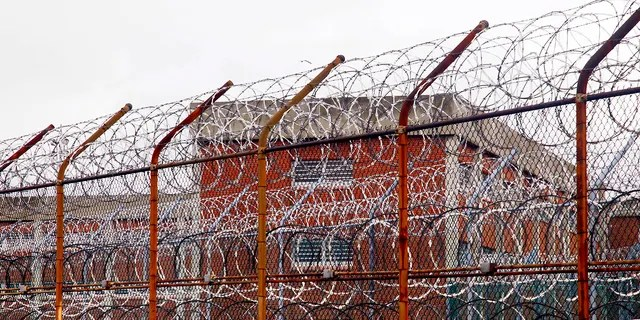 In this March 16, 2011, file photo, a security fence surrounds inmate housing on the Rikers Island correctional facility in New York. (AP Photo/Bebeto Matthews, File)
