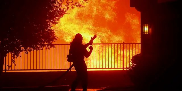 In this Thursday, Oct. 10, 2019 photo, a firefighter waits for water as the Saddleridge fire flares up near homes in Sylmar, Calif. (Associated Press)