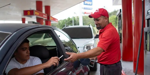In this Oct. 8, 2019 photo, gas station attendant Leowaldo Sanchez takes a cigarette as payment from a motorist as he fills the tank in San Antonio de los Altos on the outskirts of Caracas, Venezuela. This barter system, while perhaps the envy of cash-strapped drivers outside the country, is just another symptom of bedlam in Venezuela where a full tank these days costs a tiny fraction of a U.S. penny. (AP Photo/Ariana Cubillos)