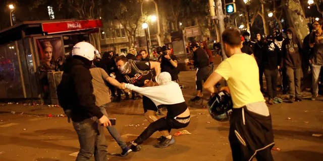 Pro-independence supporters scuffle with rioters trying to set up barricades on the street near a pro-independence demonstration in Barcelona, Spain, Saturday, Oct. 19, 2019. Radical separatists have clashed with police each night in Barcelona and other Catalan cities following huge peaceful protests of people angered by Monday's Supreme Court verdict that sentenced nine separatist leaders to prison. (AP Photo/Emilio Morenatti)