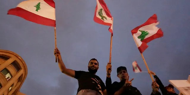 """Hezbollah supporters wave Lebanese national flag as Lebanese riot policemen separate them from anti-government protesters during a protest in Beirut, Lebanon, Thursday, Oct. 24, 2019. Lebanon's President Michel Aoun has told tens of thousands of protesters that an economic reform package put forth by the country's prime minister will be the """"first step"""" toward saving Lebanon from economic collapse. (AP Photo/Hassan Ammar)"""