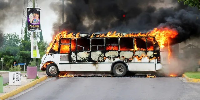 """A burning bus, set alight by cartel gunmen to block a road, is pictured during clashes with federal forces following the detention of Ovidio Guzman, son of drug kingpin Joaquin """"El Chapo"""" Guzman, in Culiacan, Sinaloa state, Mexico October 17, 2019. REUTERS/Jesus Bustamante - RC13B02793C0"""