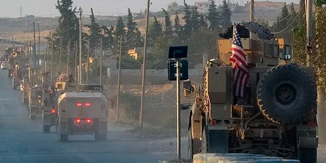 In this image from Hawar News Agency, U.S. military vehicles travel down a main road in northeast Syria on Monday.