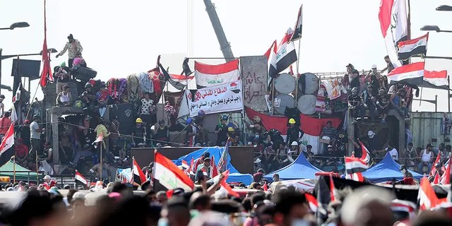 Anti-government protesters stand on barriers set by Iraqi security forces to close a bridge leading to the Green Zone government areas during ongoing protests in Baghdad, Iraq, on Monday.
