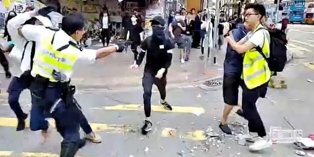 A still image from a social media video shows a police officer aiming his gun as a protester in Sai Wan Ho, Hong Kong, China November 11, 2019.