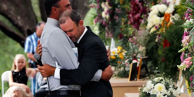 Men embraced at the first funeral for three victims of the Mexican cartel massacre. (AP Photo/Marco Ugarte)