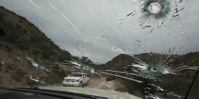 Bullet-riddled vehicles that members of the extended LeBaron family were traveling in sit parked on a dirt road near Bavispe, at the Sonora-Chihuahua state border, Mexico, Wednesday, Nov. 6, 2019. (Associated Press)