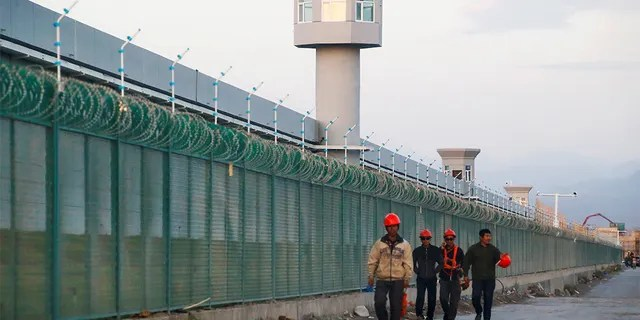 FILE PHOTO: Workers walk by the perimeter fence of what is officially known as a vocational skills education centre in Dabancheng in Xinjiang Uighur Autonomous Region, China September 4, 2018. This centre, situated between regional capital Urumqi and tourist spot Turpan, is among the largest known ones, and was still undergoing extensive construction and expansion at the time the photo was taken. Picture taken September 4, 2018. REUTERS/Thomas Peter/File Photo - RC112C876810