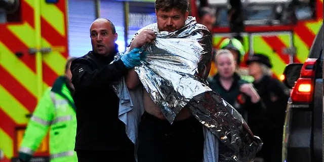 Police assist an injured man near London Bridge in London, on November 29, 2019 after reports of shots being fired on London Bridge. - The Metropolitan Police on Friday said several people were injured and a man was held after a stabbing near London Bridge in the centre of the British capital. (Photo by DANIEL SORABJI / AFP) (Photo by DANIEL SORABJI/AFP via Getty Images)