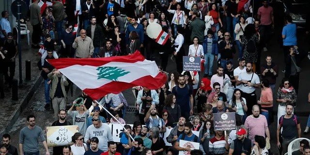 Lebanese protesters wave their national flag, as they march in Beirut, Lebanon on Sunday. (AP Photo/Hussein Malla)