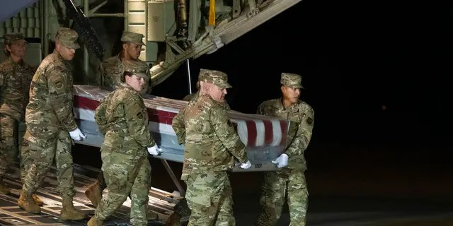 An Air Force carry team moves the transfer case containing the remains of Navy Seaman Apprentice Cameron Scott Walters, of Richmond Hill, Ga., Sunday, Dec. 8, 2019, at Dover Air Force Base, Del. A Saudi gunman killed three people including Walters in a shooting at Naval Air Station Pensacola in Florida.