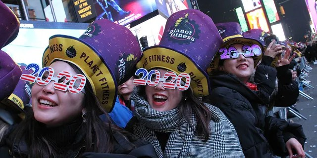 Revelers, including Natsumi Ishikawa, left, and Minori Kondo, second from left, both from Nagoya, Japan, take part in the New Year's Eve festivities in New York's Times Square, Tuesday, Dec. 31, 2019. Celebrations this year have been disrupted by the COVID-19 pandemic and the threat of winter storms. (AP Photo/Tina Fineberg)