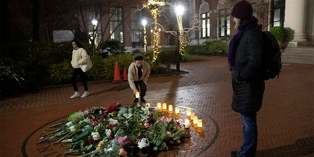People pause and place a candle at a makeshift memorial for Tessa Majors inside the Barnard campus.