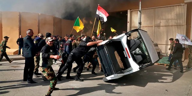 Protesters damage property inside the U.S. embassy compound, in Baghdad, Iraq, on Tuesday.