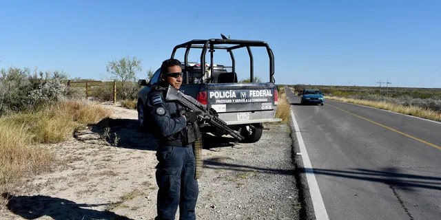 Police guard the highway leading to ViIlla Union, Mexico, Sunday, Dec. 1, 2019, the day after it was assaulted by gunmen.