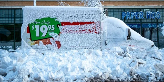A U-Haul truck sits snowed in by plows on First Street in downtown Duluth, Minn., on Sunday, Dec. 1, 2019.