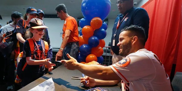 Jose Altuve signs autographs for young fans during the baseball team's FanFest at Minute Maid Park on Saturday, Jan. 18, 2020, in Houston. (Associated Press)