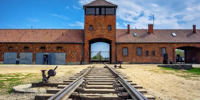 The main gate to the nazi concentration camp of Auschwitz Birkenau with train rail, Poland.
