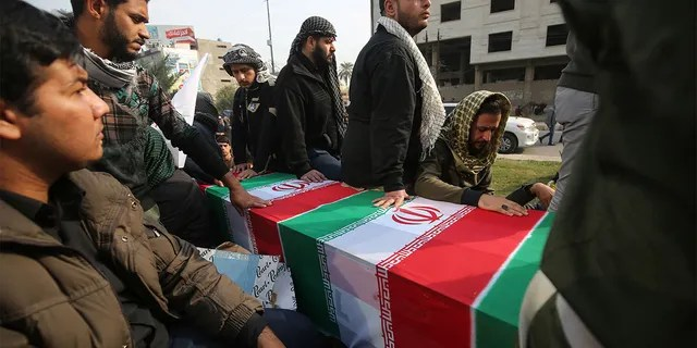 """Iraqis surround a coffin, draped in an Iranian national flag, during the funeral procession of Iraqi paramilitary chief Abu Mahdi al-Muhandis, Iranian military commander Qasem Soleimani, and eight others, in the capital Baghdad's district of al-Jadriya, near the high-security Green Zone, on January 4, 2020. - Thousands of Iraqis chanting """"Death to America"""" joined the funeral procession for Iranian military commander Qasem Soleimani and Muhandis, both killed in a US air strike. The cortege set off around Kadhimiya, a Shiite pilgrimage district of Baghdad, before heading to the Green Zone government and diplomatic district where a state funeral was to be held attended by top dignitaries. In all, 10 people -- five Iraqis and five Iranians -- were killed in Friday morning's US strike on their motorcade just outside Baghdad airport. (Photo by AHMAD AL-RUBAYE / AFP) (Photo by AHMAD AL-RUBAYE/AFP via Getty Images)"""