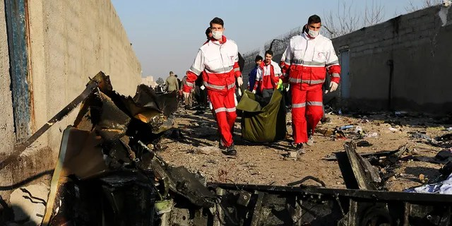 Rescue workers carry the body of a victim of an Ukrainian plane crash among debris of the plane in Shahedshahr, southwest of the capital Tehran, Iran, Wednesday, Jan. 8, 2020. (AP Photo/Ebrahim Noroozi)
