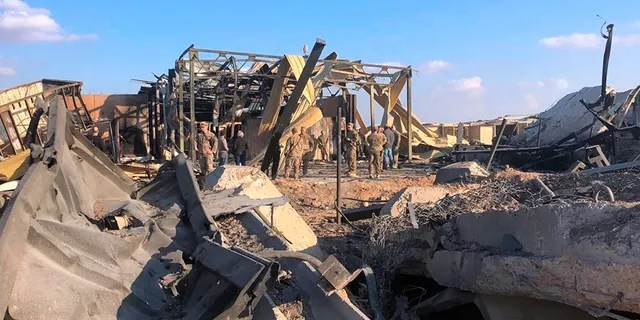U.S. soldiers and journalists inspect the rubble at a site of Iranian bombing, in Ain al-Asad base in Anbar, Iraq, on Monday. (AP)