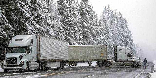Semitrailer trucks that had been waiting at the U.S. 2 closure turn around Monday, Jan. 13, 2020, in Gold Bar, Wash. after the highway was closed indefinitely.